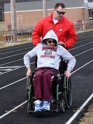 Coach Mat Dunham helps Braedon Pollmann during warm