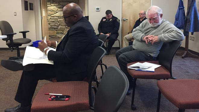 City Councilman Keith Young, left, and neighborhood activist Mike Lewis, right, look over paperwork during a pause in a meeting Thursday of the Buncombe County Board of Elections. Lewis is challenging whether Young lives inside the city limits.