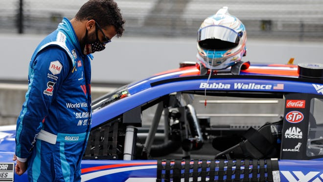 Bubba Wallace stands next to his car during a prayer before a NASCAR Cup Series auto race at Indianapolis Motor Speedway in Indianapolis, Sunday, July 5, 2020.