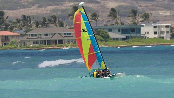 A Hobie Cat sailboat cruises off the beach in Kailua, Hawaii.