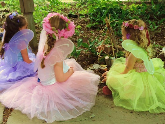 Little girls gather to admire the fairy houses at Fairy Day at Frelinghuysen Arboretum.