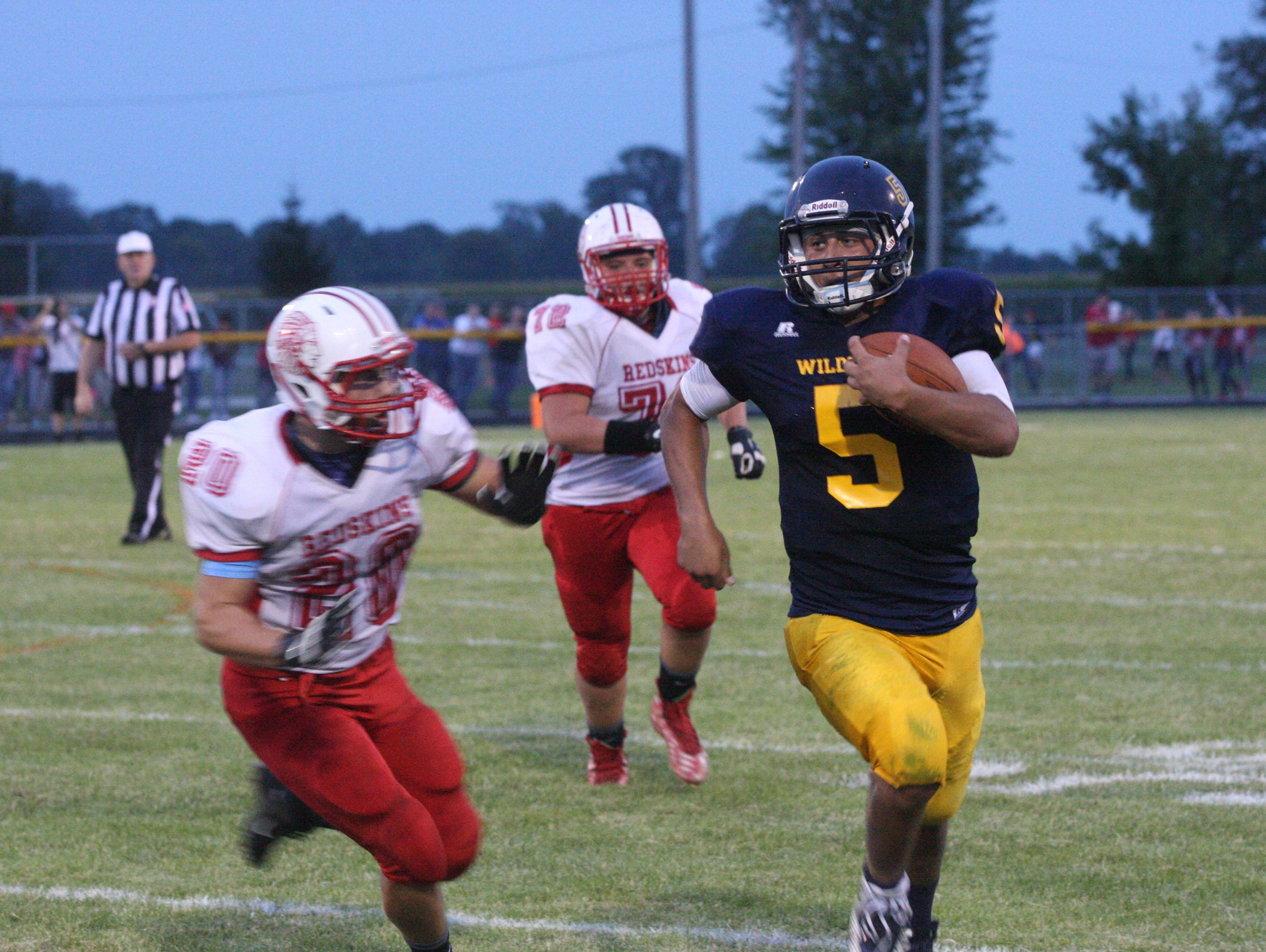 Woodmore quarterback Conner Bringman rushes for yardage against Port Clinton's Jacob McCoy in Week 1.