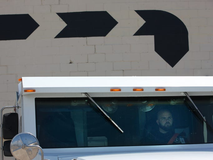Blue Line Protection Group's supervisor of operations, Matt Karr, waits in the armored car as Philip Baca (not pictured) makes a delivery at a marijuana dispensary in Colorado. As of Jan. 1, state residents can legally buy and possess up to an ounce of marijuana at a time.
