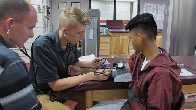 Teacher Shawn Fahey, left, observes as Ryan Drusky, 17, takes the pulse of Justin Martinez, 16, in the Sports Medicine Exercise Science program, in this photo taken in 2018, when the program started. This year, classes will be a blend of remote learning and in-person due to the pandemic.