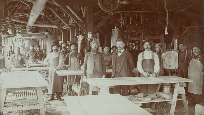Interior view showing workers in the door department of Paine Lumber Company in Oshkosh.