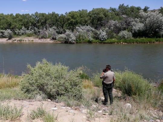 San Juan County Sheriff's Office Deputy Russ Bradford talks with fellow officers on Friday during a manhunt along the Animas River in Farmington for a suspect accused of trying to run over a police officer with a car.