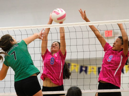 Farmington's Bergen Campbell attempts to spike the ball past Bloomfield's Elena Florez and Taneesha Valdez on Tuesday at Bobcat Gym in Bloomfield.