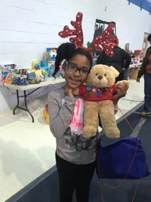 Kamara Doyle, 9, holding the cub that she made through the Create-A-Cub station during a toy distribution event held by Bridgeton African American Union and Mid-Atlantic Pain Specialists.