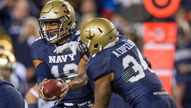 Navy Midshipmen quarterback Keenan Reynolds (19) hands off to fullback Noah Copeland (34) in the first quarter against the Notre Dame Fighting Irish at FedEx Field.
