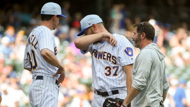 Milwaukee Brewers manager Craig Counsell talks to pitcher Adrian Houser (37) who fell ill during the game against the Philadelphia Phillies in the eighth inning at Miller Park.