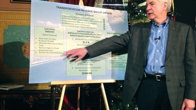 Michigan Gov. Rick Snyder explains the transportation department's revenue budget ballot option during a news conference in Lansing, Mich., Thursday, Dec. 18, 2014. (AP Photo/David Eggert)