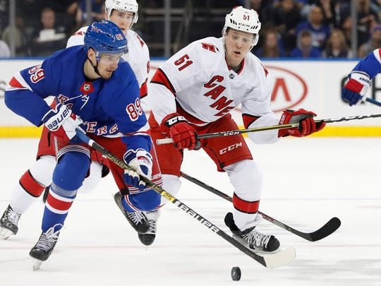Carolina Hurricanes defenseman Jake Gardiner (51) chases New York Rangers right wing Pavel Buchnevich (89) during the second period of an NHL hockey game Friday, Dec. 27, 2019, in New York. (AP Photo/Kathy Willens)