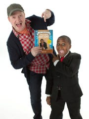 "Co-authors Brad Montague and Robby Novak pose with a copy of ""Kid President's Guide to Being Awesome."""