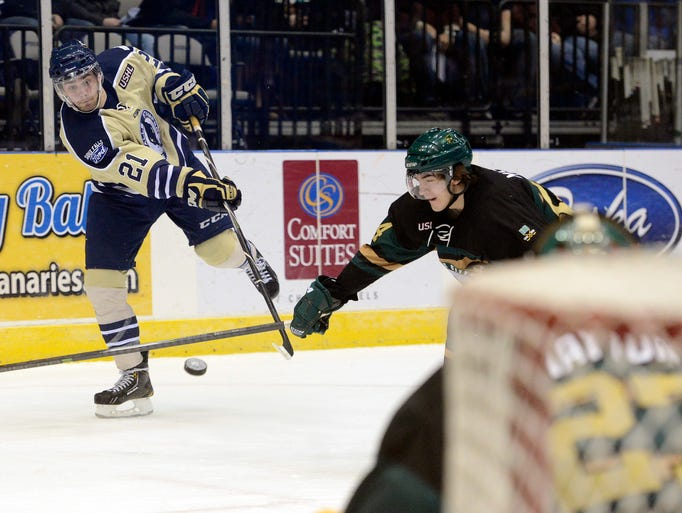 The Stampede's Christian Horn takes a shot on goal past Sioux City's Tyler Mueller in Friday night's game at the Sioux Falls Arena, March 28, 2014.