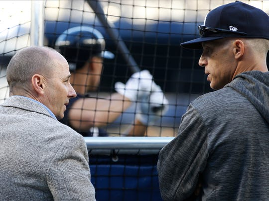 New York Yankees general manager Brian Cashman, left, and manager Joe Girardi, right, chat behind the batting cage while Yankees' Aaron Judge takes batting practice before the American League wild-card playoff baseball game against the Minnesota Twins in New York, Tuesday, Oct. 3, 2017.