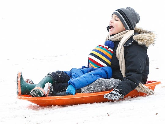 Sledders enjoying the sleet and snow that hit the Memphis area Friday, as they slide inside the Levitt Shell.