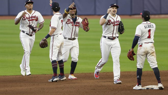 Atlanta Braves' Ozzie Albies (1) celebrates with teammates after Game 2 of a baseball National League Division Series against the Miami Marlins Wednesday, Oct. 7, 2020, in Houston. The Braves won 2-0.
