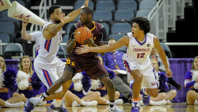 Evansville Aces guard Christian Benzon (2) and Evansville Aces guard Dru Smith (12) guard Loyola Ramblers guard Milton Doyle (35) during their game at the Ford Center in Evansville, Wednesday, Feb. 8, 2017. Evansville beat Loyola 60-58.
