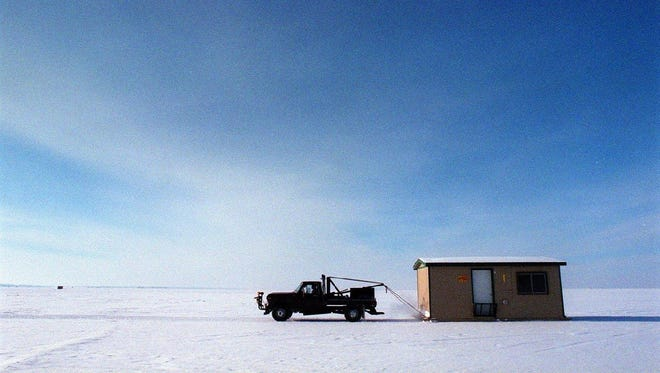 During a previous season, a resort truck pulls a fish house onto Mille Lacs Lake. So far this year, only foot traffic and the occasional ATV has ventured onto the ice.