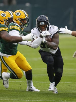 Jacksonville Jaguars rookie running back James Robinson (30) runs through a small hole Sunday, Nov 15, 2020, against the Green Bay Packers in Green Bay, Wis.