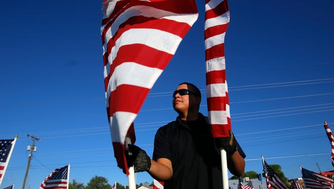 Volunteer Corie James helps set up a flag on Friday for the Rotary Club and Blue Star Mothers' Healing Fields event at the Farmington Boys and Girls Club.