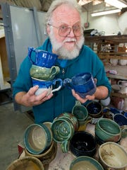 Pensacola State College's Bill Clover with a variety of bowls created for Manna fundraisers.
