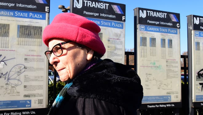Rachel Lawrence, 82, of Teaneck reads the bus route information at the Garden State Plaza mall bus stop after taking the bus from Englewood.