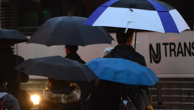 Commuters wait in the rain for the NJ Transit bus to New York City in Rutherford Tuesday morning, January 23, 2018.