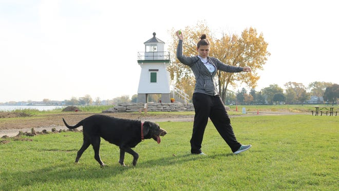 Ellie Riser, of Fostoria, and her 10-year old dog, Lucy, play a game of fetch at Waterworks Park during an unseasonably warm day in November on Tuesday.