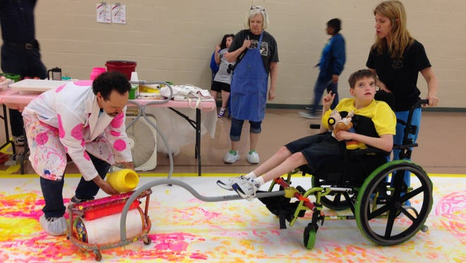Artist Dwayne Zot (left) pours yellow paint onto a foam roller that Scooter P., a student at the Louisiana Special Education Center in Alexandria, will use to paint a pattern across a canvas on a gym floor in the school with help from his teacher, Ann Sehon. Zot creates adaptive art tools through his studio, Zot Artz. He led art activities at the school Monday.