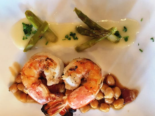 Grilled tiger prawns is served with garbanzo beans, applewood bacon, pickled asparagus and mirin‐beurre blanc (a zesty sauce with a rice wine base) at the Grand Union Hotel's restaurant, the Union Grille.