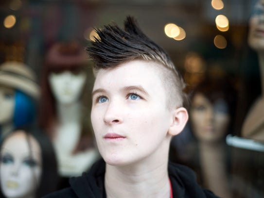 Rory Philbrick stands outside a wig shop by the corner