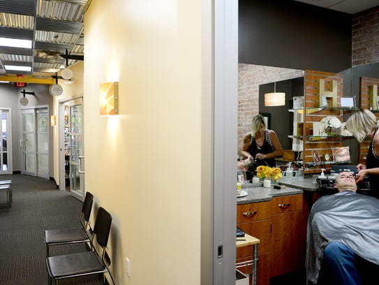 Anna Diggs, owner of Hue Color Lounge, washes Jeff