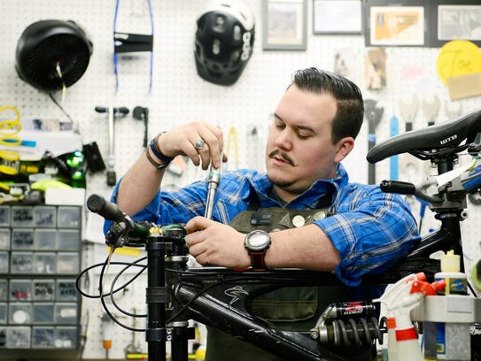 Joe Fiato, a certified technician, works on a bicycle