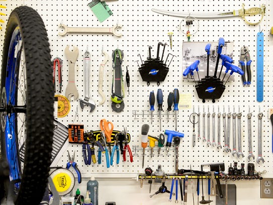 Bicycle tools are hung on a wall in the bicycle shop