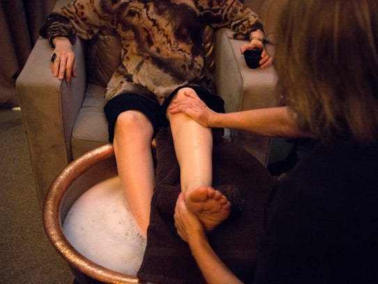 Massage therapist Genny Gray rubs down the foot of