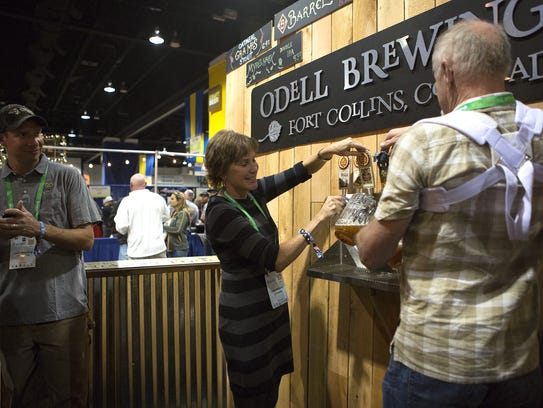 Owner Wynne Odell of Odell Brewing pours beer at the