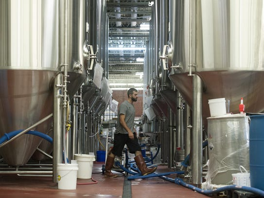 Steven Anan, head of Cellar at Hi-Wire Brewing, cleans