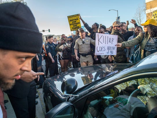 Protesters surround a police car as they shut down