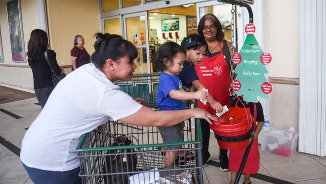 Brothers Hoben, 3, and Kayden Tenorio, 1, help their mother, Christen Naputi, place donations into The Salvation Army Red Kettle and volunteer bellringers Barbara Santos and her grandson, Gaven Santos, watch at an entrance to the Agana Shopping Center on Friday, Nov. 24, 2017. The Salvation Army kicked off this year's Red Kettle campaign with a ceremony held within the mall's centercourt moments before. The goal for this year's campaign has been set at $70,000 by The Salvation Army.