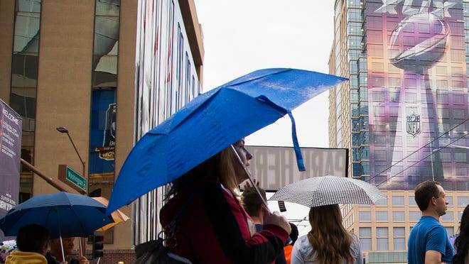 People make their way with umbrellas up as a light rain hits at Super Bowl Central in Phoenix, AZ on January 29, 2015.