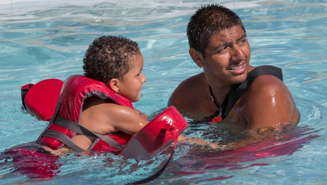 Lifeguard Raul Flores helps Jaylen Hernandez, 4, back after the waterside at Cortez Pool in Phoenix in a 2014 photo. The city will be looking to staff its 29 public pools for the upcoming swim season.