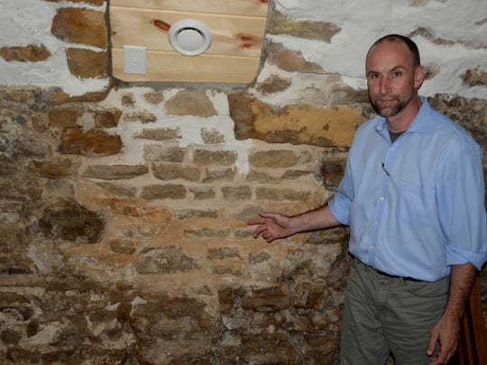 Stamm House manager Craig Madigan points out the bricked-in Underground Railroad tunnel in the historic restaurant.