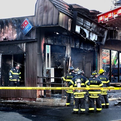 Firefighters work at the scene of the Domino's Pizza restaurant fire in Wappingers Falls on April 16, where Adam Justiniano died in the blaze.