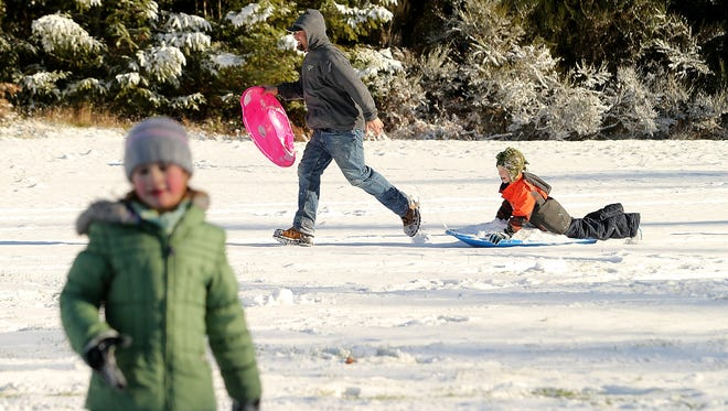 Ryan Feathers carries daughter Stella Mae's sled while pulling neighbor Caleb Paulus, 9, on his sled as they head back up the hill during a snow day at Silver Ridge Elementary School in Silverdale on Thursday, Feb. 22, 2018.