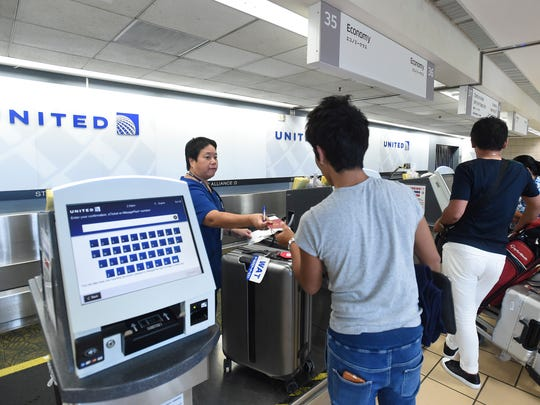 Sharon Sugiyama, the United Airlines customer service team leader, assists a passenger at the check-in counter, in the Antonio B. Won Pat International Airport on June 25, 2018.