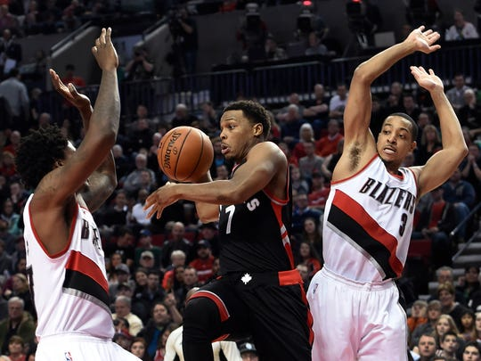 Toronto Raptors guard Kyle Lowry (7) drives to the basket on Portland Trail Blazers center Ed Davis, left, and guard C.J. McCollum (3) during the second half of an NBA basketball game in Portland, Ore., Thursday, Feb. 4, 2016. The Raptors won 110-103.