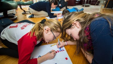 Elizabeth Cunningham, 9, left ,and sister Hannah, 10, join their mother Alicia Cunnigham, center, and their sister Rebecca and brother William as they make signs at home in Burlington on Wednesday, January 18, 2017, in advance of Saturday's Women's March on Washington in Washington D.C. Hannah will be attending the march with her mother and sister Rebecca.