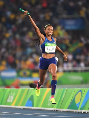 Allyson Felix crosses the finish line in the 4x400 relay.
