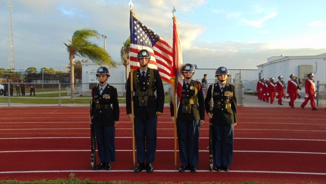 The Port St. Lucie High School Color Guard waits to march onto the field before the game.